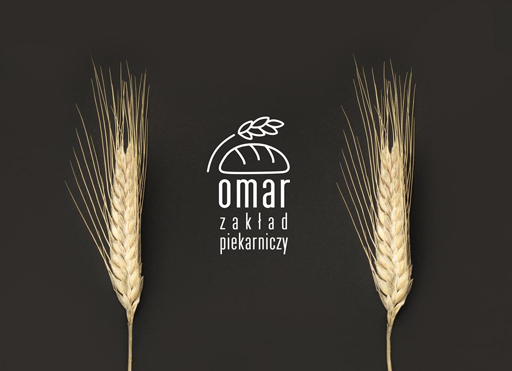 Prezentacja logo piekarni OMAR na czarnym tle z ułożonymi obok kłosami